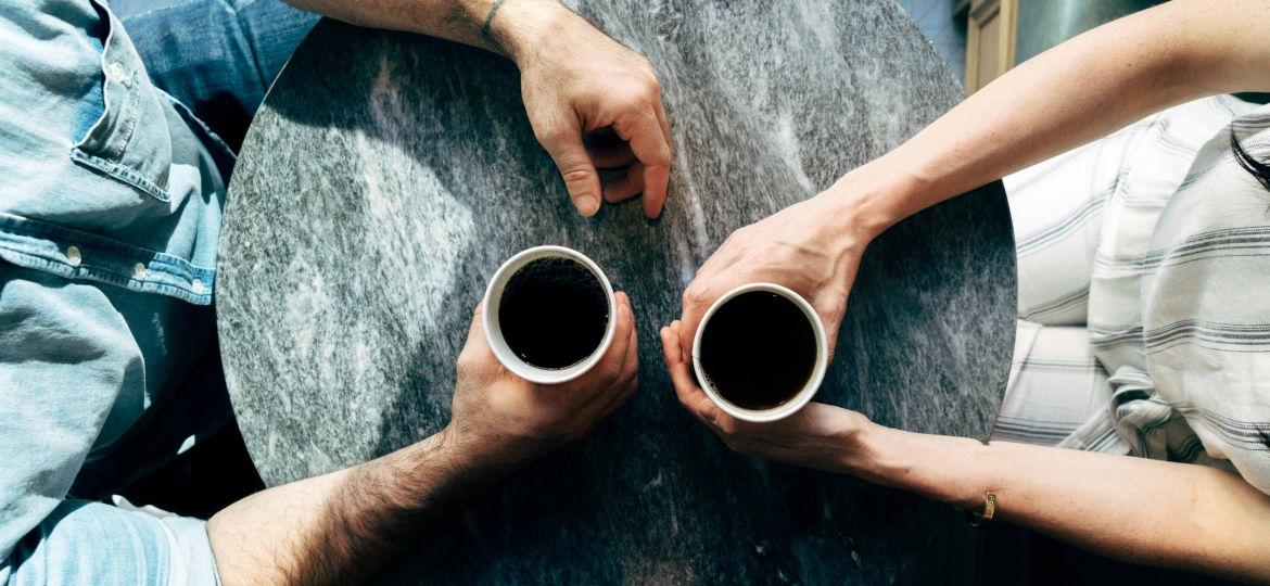 Two people holding coffee cups on top of a round table